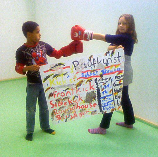 Zwei Kinder mit selbstgemalten Plakat in Boxstellung