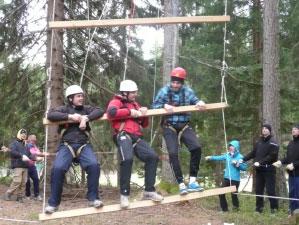 Jugendliche klettern auf eine Strickleiter im Wald